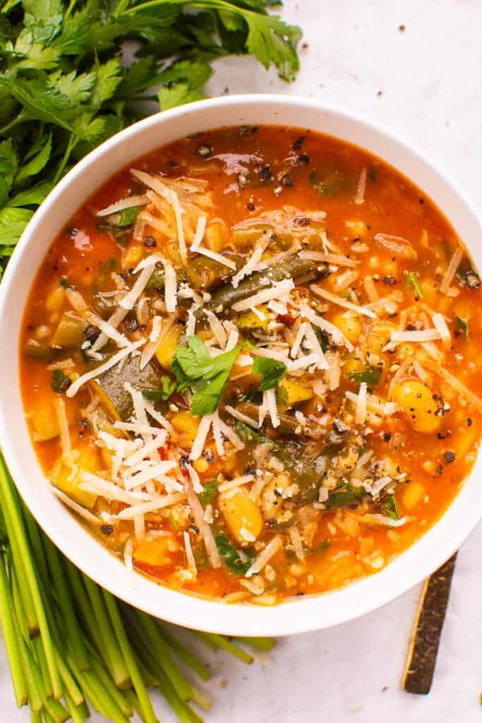 minestrone soup in a bowl with herbs beside bowl