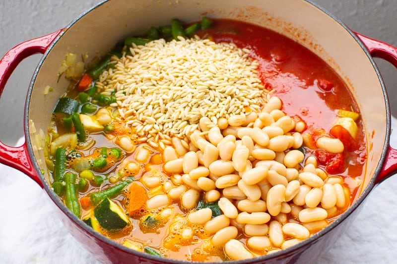cannellini beans, veggies, pasta, tomato broth in red pot