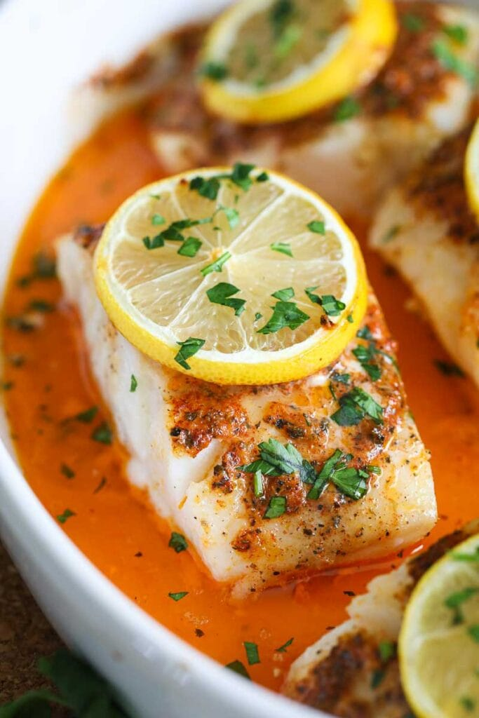 close up image of baked cod with a slice of lemon and chopped parsley on top