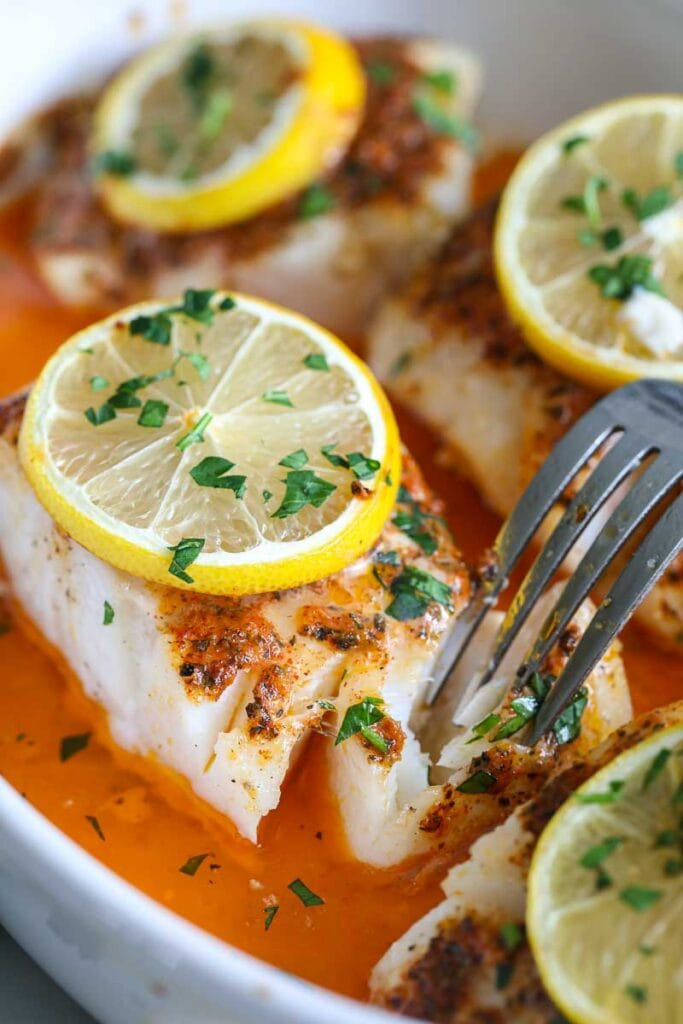 close up image of oven baked cod with lemon and parsley on top