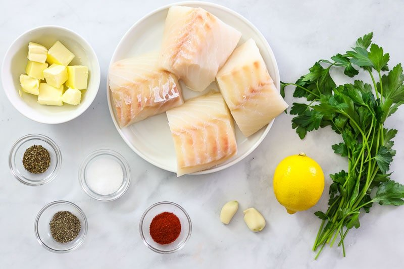 An overhead image of baked cod ingredients on a white background