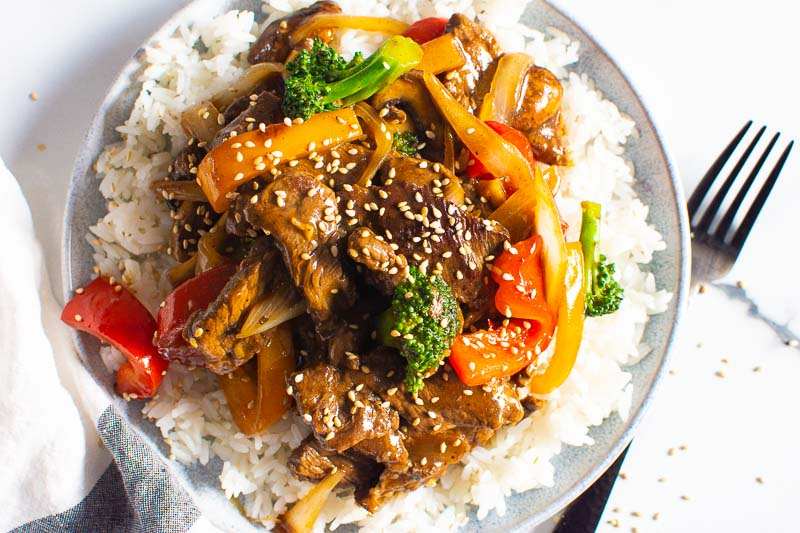 beef stir fry with rice and sesame seeds on a plate