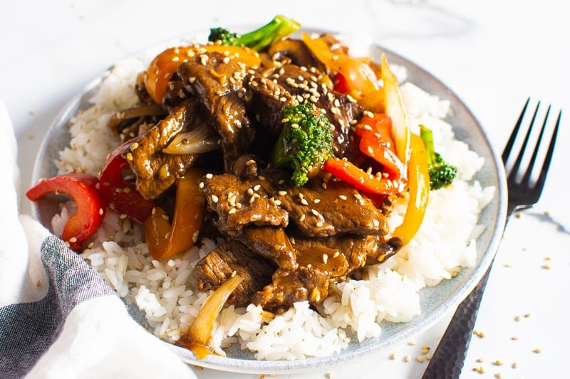 beef stir fry served over white rice on white and blue plate