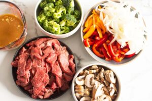 sliced beef, mushrooms, onion, peppers, broccoli and stir fry sauce in bowls