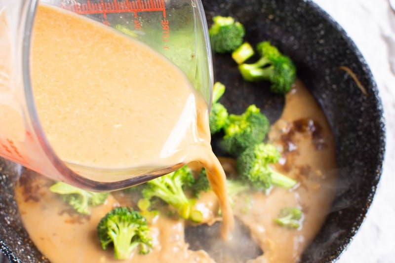 pouring stir fry sauce over broccoli in black skillet
