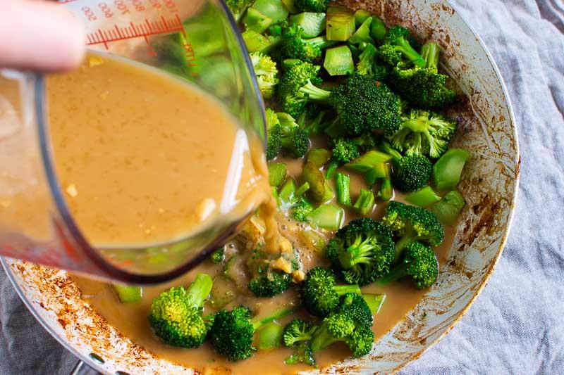 vertiendo salsa para saltear en una sartén con brócoli