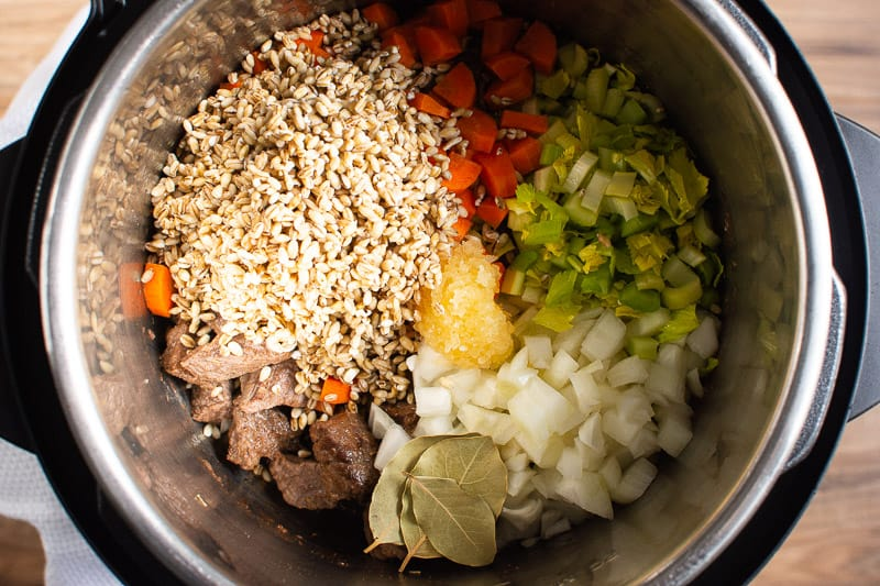 barley, carrots, celery, onion, garlic, bay leaves in Instant Pot