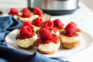 instant pot cheesecake bites with raspberries on white plate
