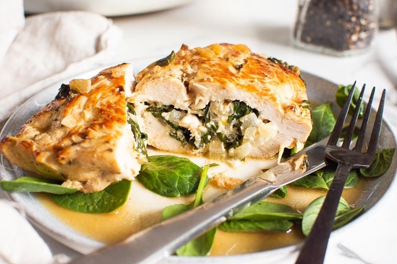 sliced in half spinach stuffed chicken breast served on a plate