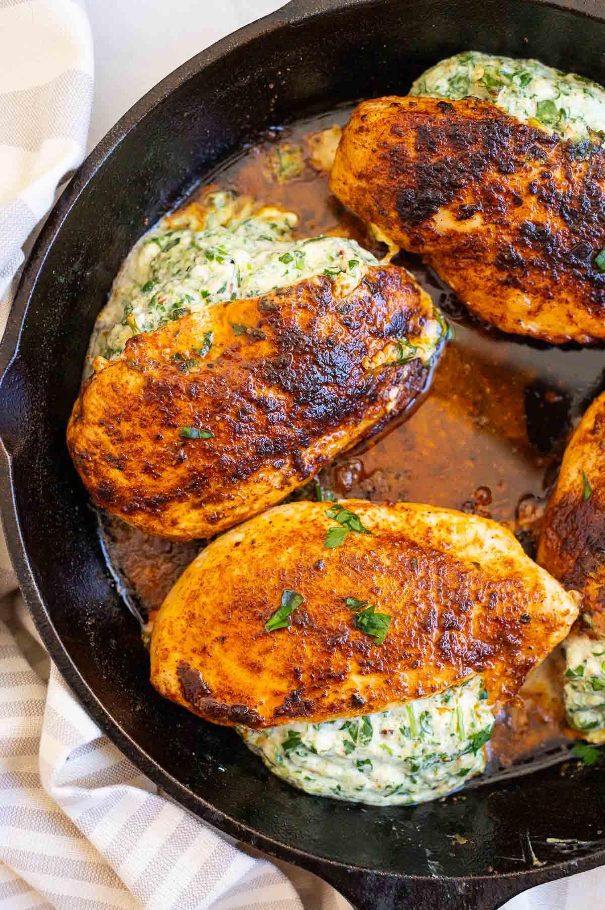 spinach stuffed chicken breast in white skillet with gravy