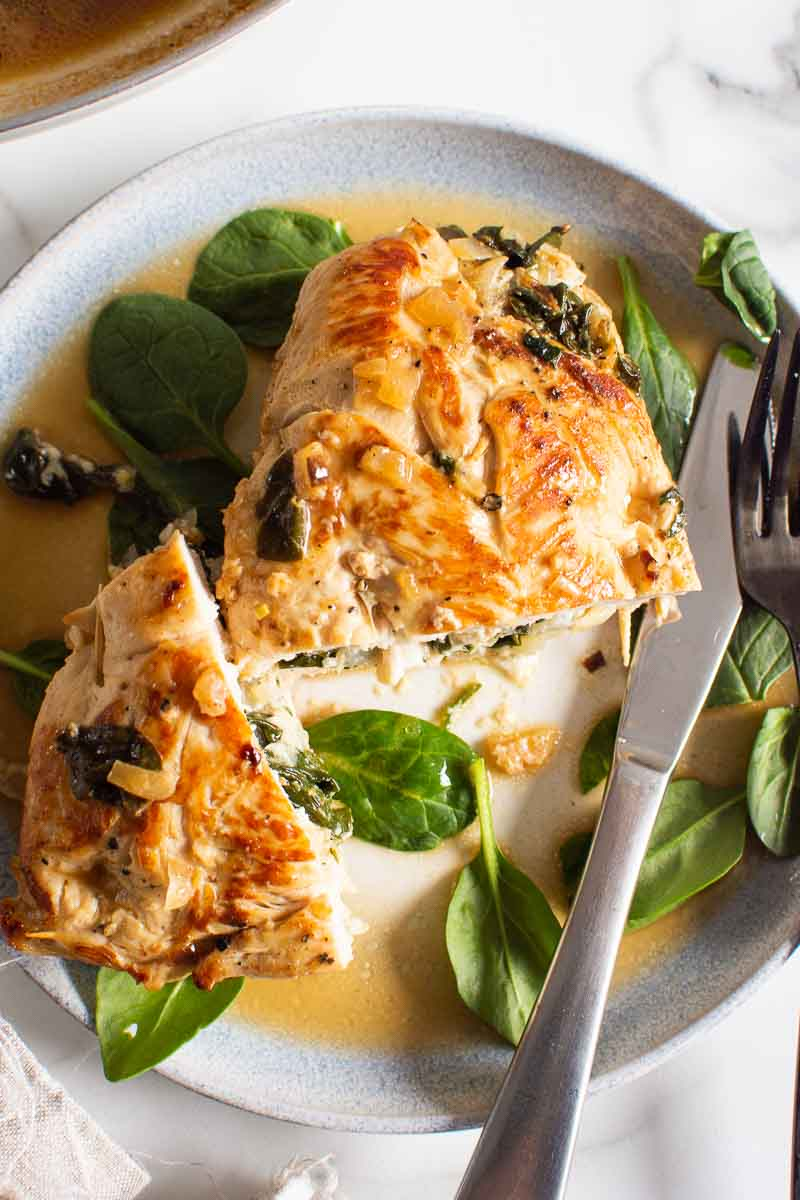 spinach stuffed chicken breast on a plate with fork and knife