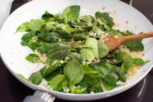 sauteed onion, garlic, spinach and spices in white skillet with wooden spoon