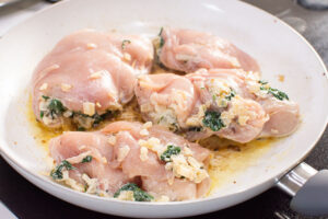spinach stuffed chicken breast frying in white pan