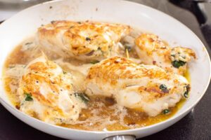 spinach stuffed chicken breast simmering in broth