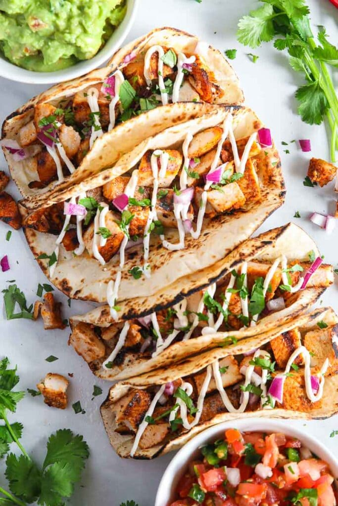 Chicken Tacos on a plate with guacamole to the side.