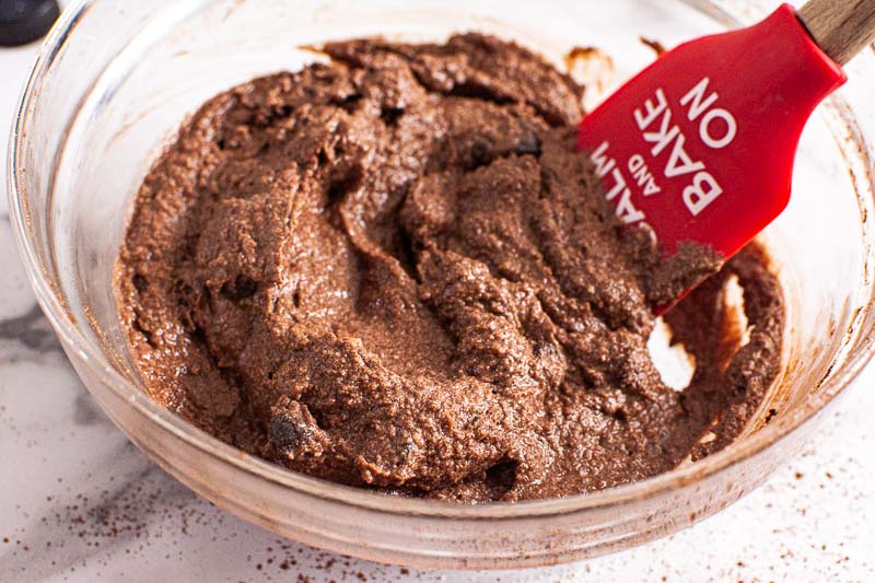 almond flour brownies batter in glass bowl with red spatula
