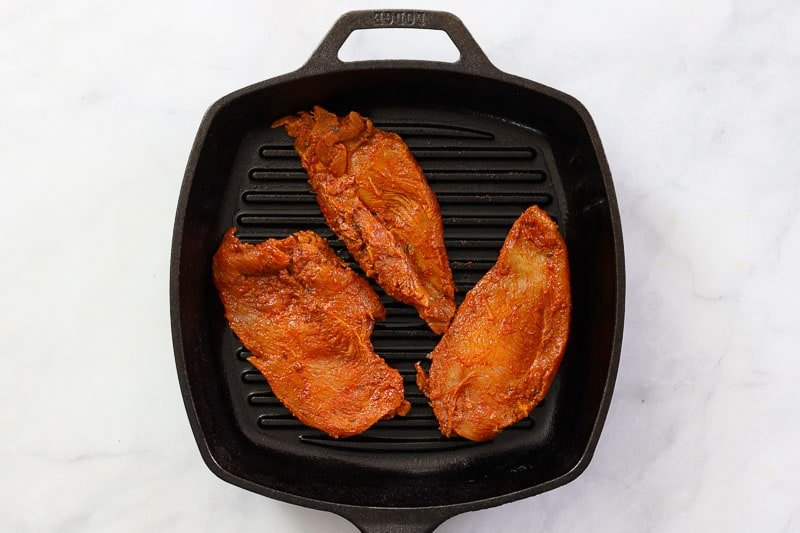Chicken breasts on a cast iron pan to make Chicken Tacos.