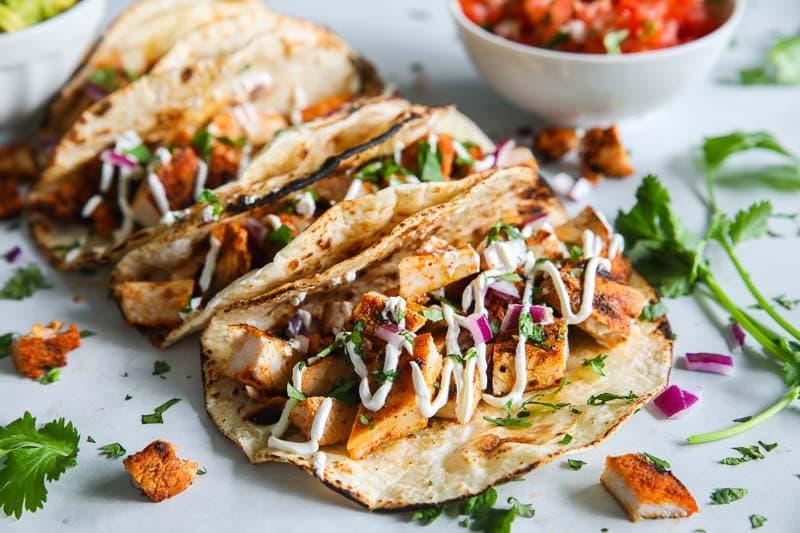 Closeup of Chicken Tacos with some cilantro and pico de gallo in the background.