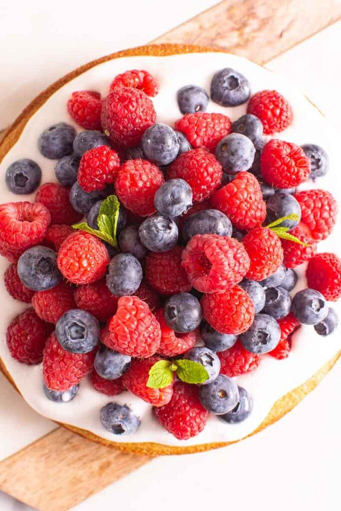 almond cake with fresh berries on marble platter