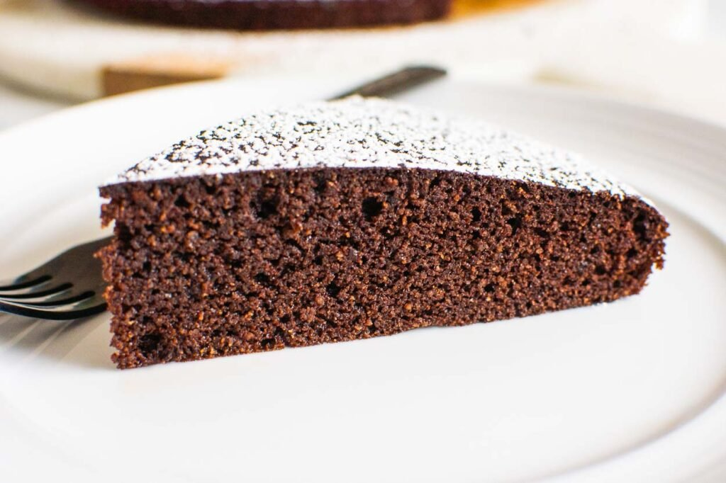 a slice of gluten free chocolate cake on a plate with work