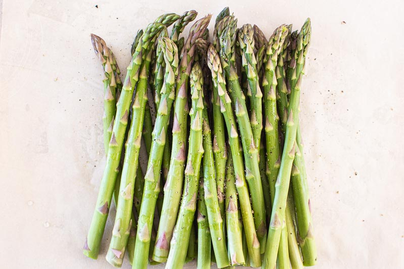 a bunch of trimmed asparagus with oil, salt and pepper