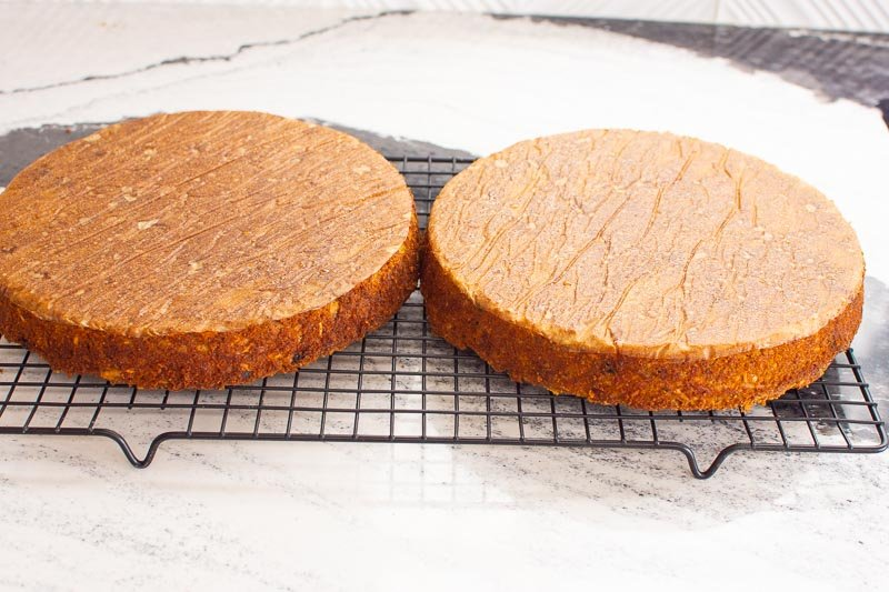 2 baked gluten free carrot cakes cooling on a rack