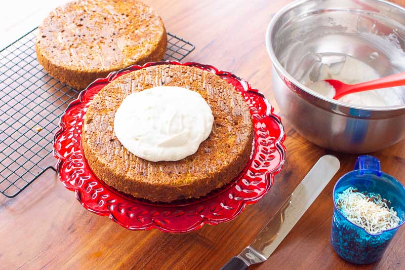 almond flour carrot cake, frosting and garnishes in bowls