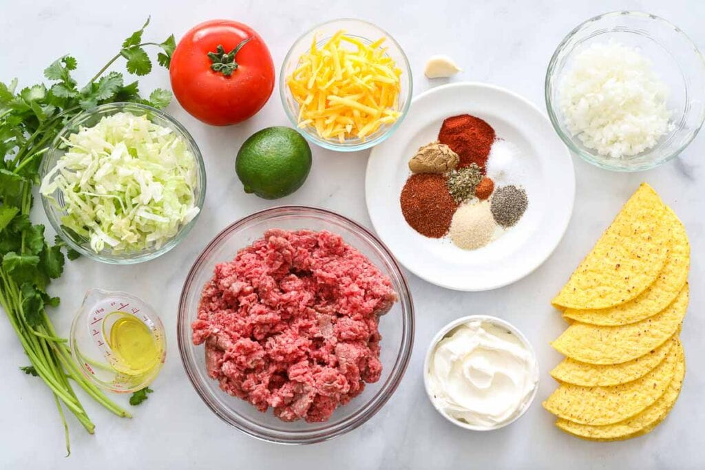 Ingredients for Ground Beef Tacos, including beef, cheese, taco shells, seasonings, sour cream, onion, garlic, tomatoes, lettuce, cilantro, lime, and oil.
