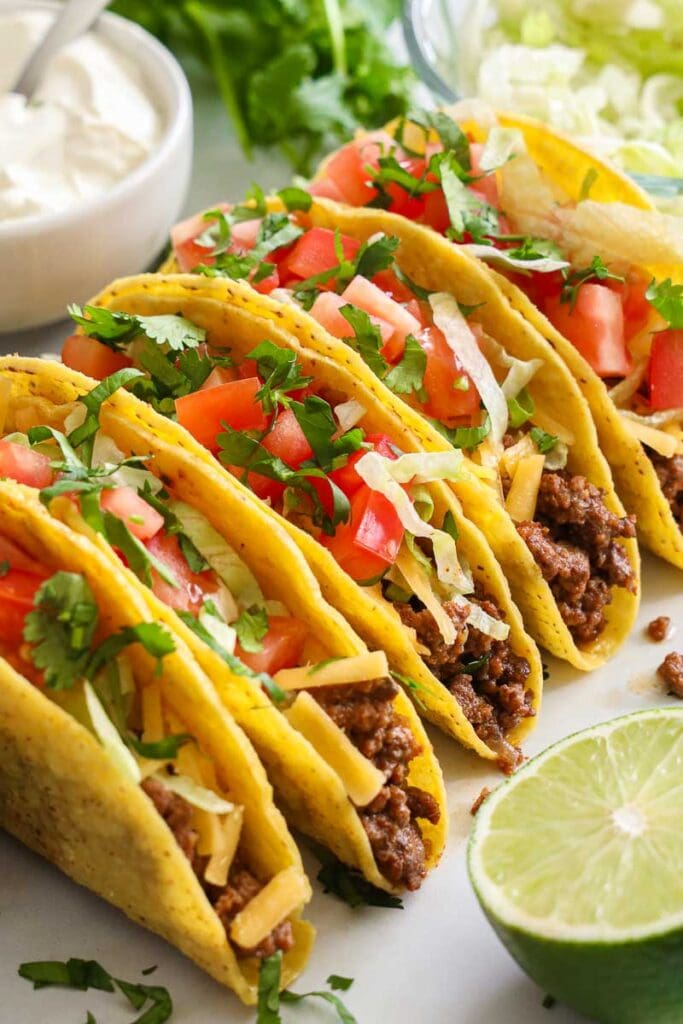 Ground Beef Tacos lined up with toppings