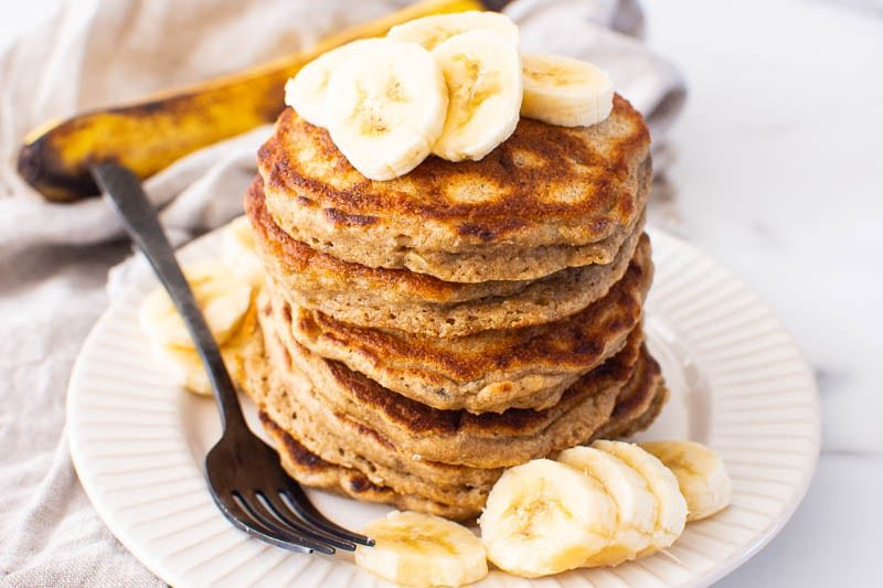 healthy banana pancakes served on white plate with sliced bananas