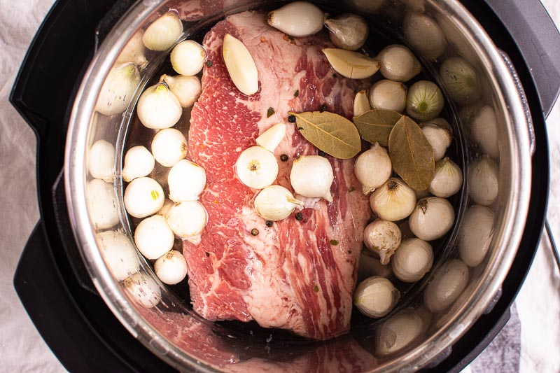 uncooked brisket with onions, garlic and peppercorns in instant pot