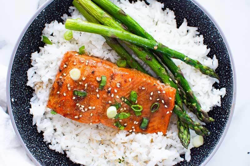 teriyaki salmon with rice and asparagus in black bowl