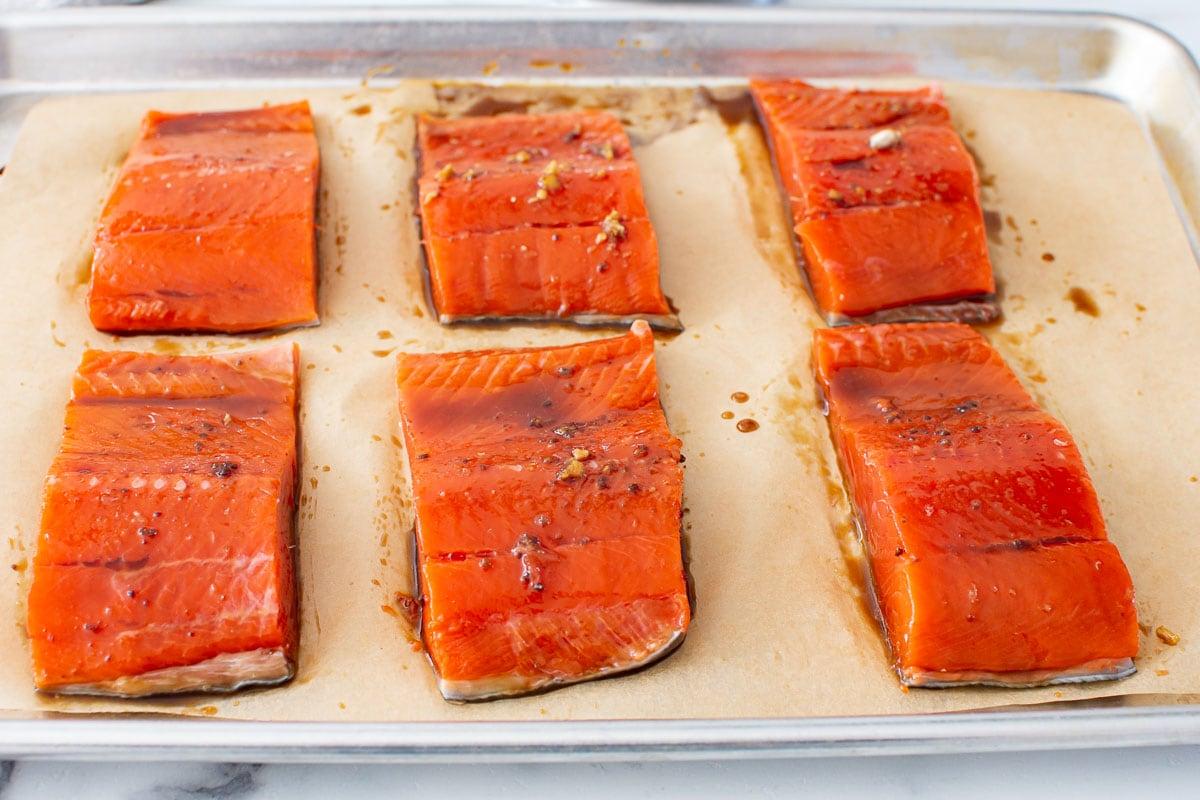uncooked teriyaki salmon on baking sheet
