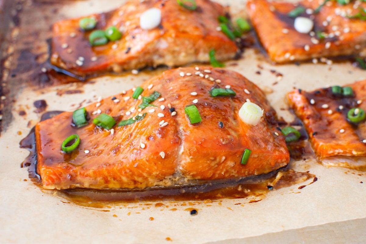 teriyaki salmon with sesame seeds and green onion on baking sheet