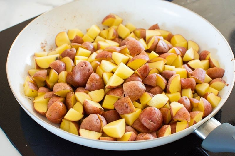 cubed red baby potatoes in white skillet