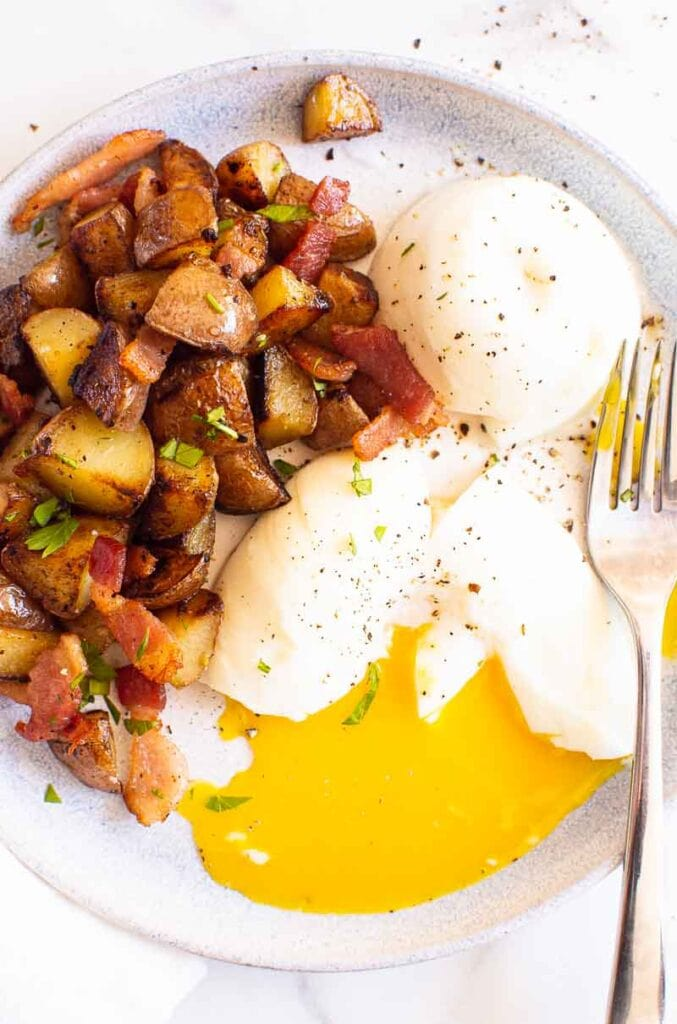 breakfast potatoes served with poached eggs on white blue plate