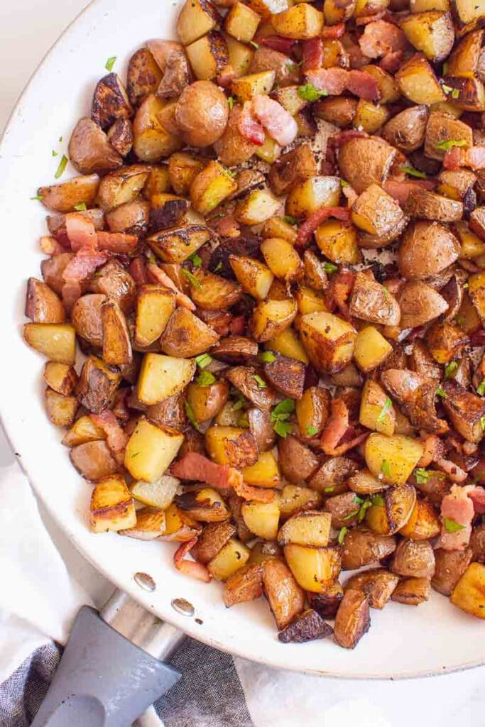Ukrainian breakfast potatoes with bacon in white skillet