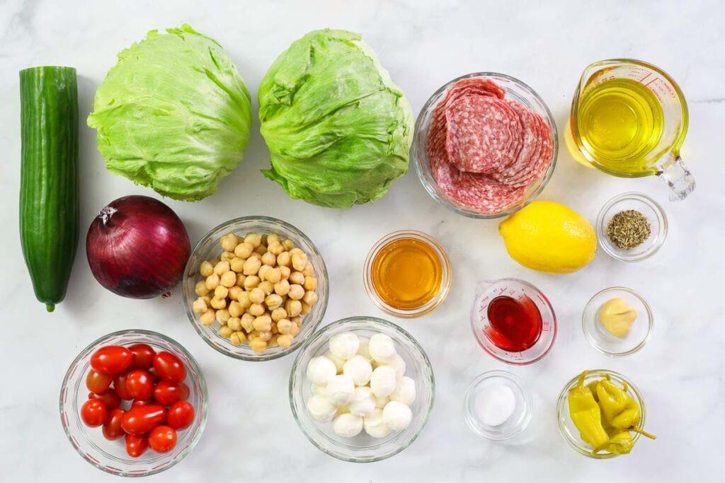 Ingredients for Italian Chopped Salad, including iceberg lettuce, cucumber, red onion, salami, mozzarella pearls, garbanzo beans, cherry tomatoes, pepperoncini, lemon, olive oil, red wine vinegar, honey, salt, and Italian seasoning.