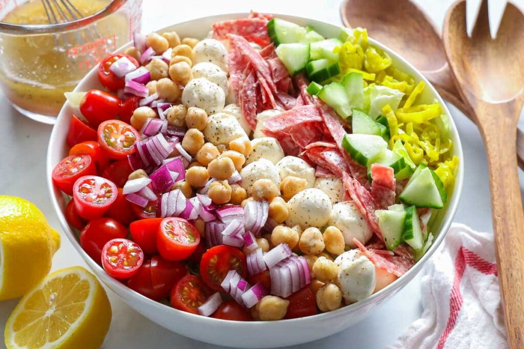 Steps to make Italian Chopped Salad, including assembling the salad and tossing it with dressing.