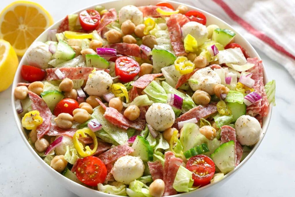 Italian Chopped Salad in a white bowl with sliced lemons beside it