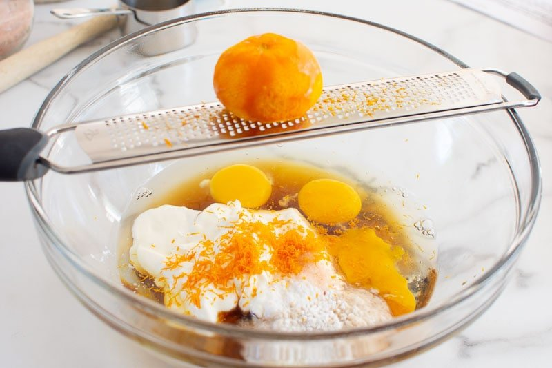 zesting orange over a bowl with baking ingredients