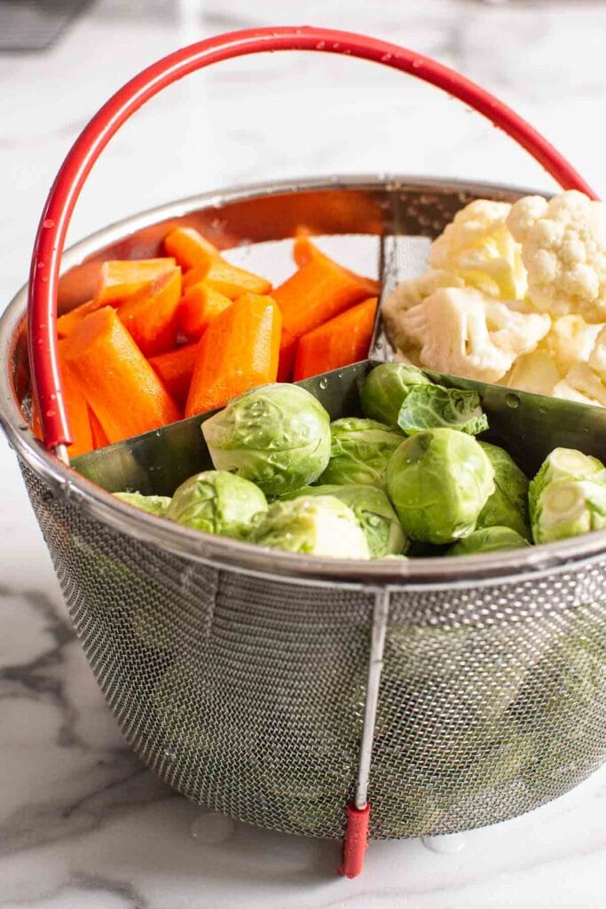 raw brussels sprouts, cauliflower and carrots in mesh basket