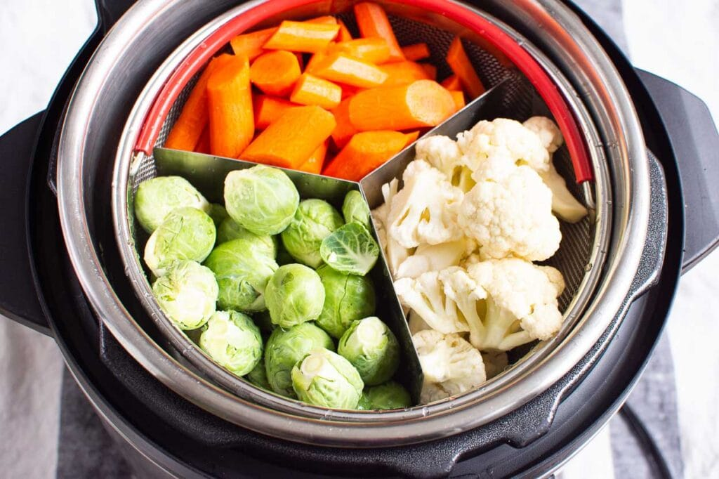raw vegetables in mesh basket inside pressure cooker