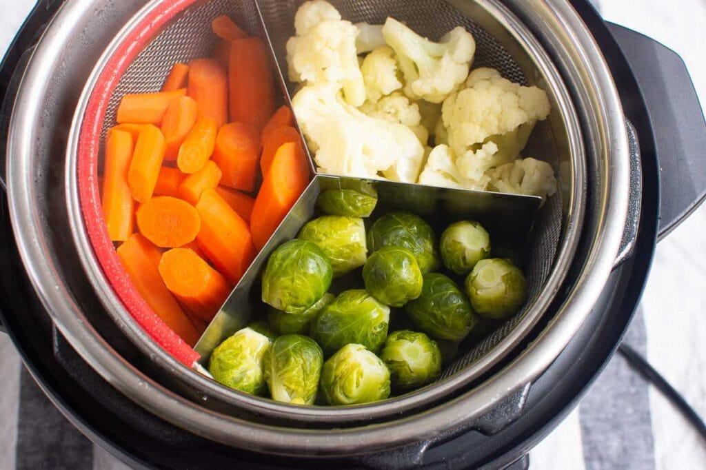 cooked vegetables in mesh basket inside pressure cooker