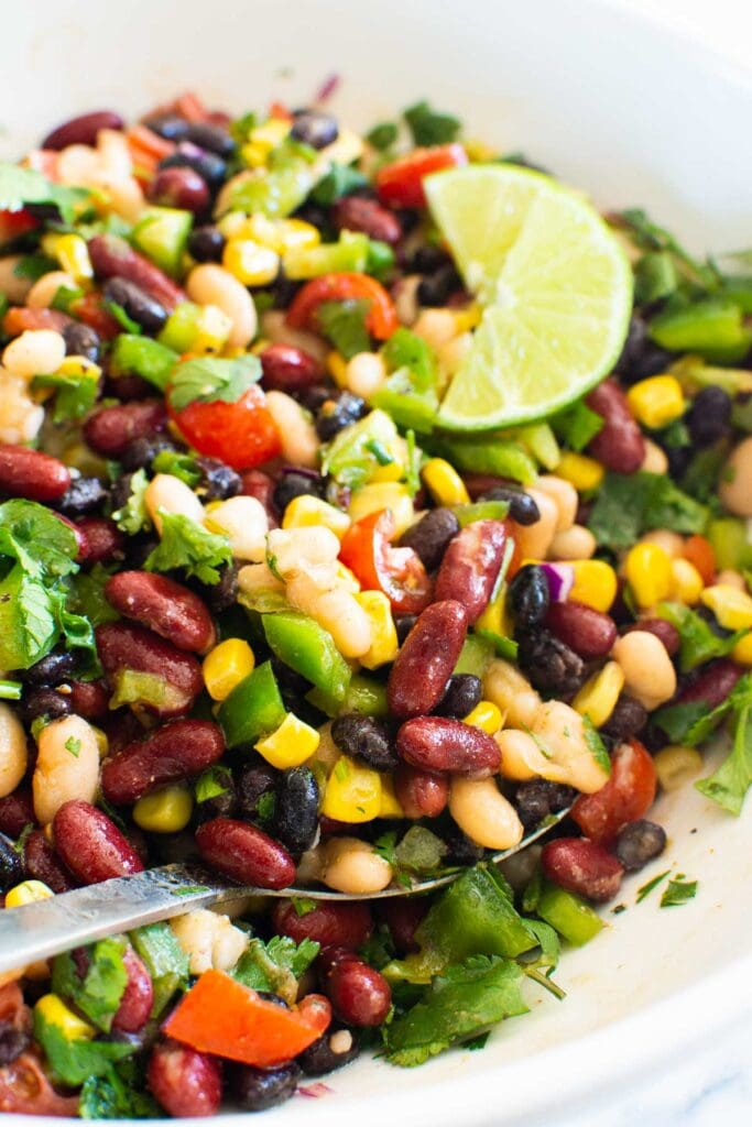 spoon with mexican corn and black bean salad
