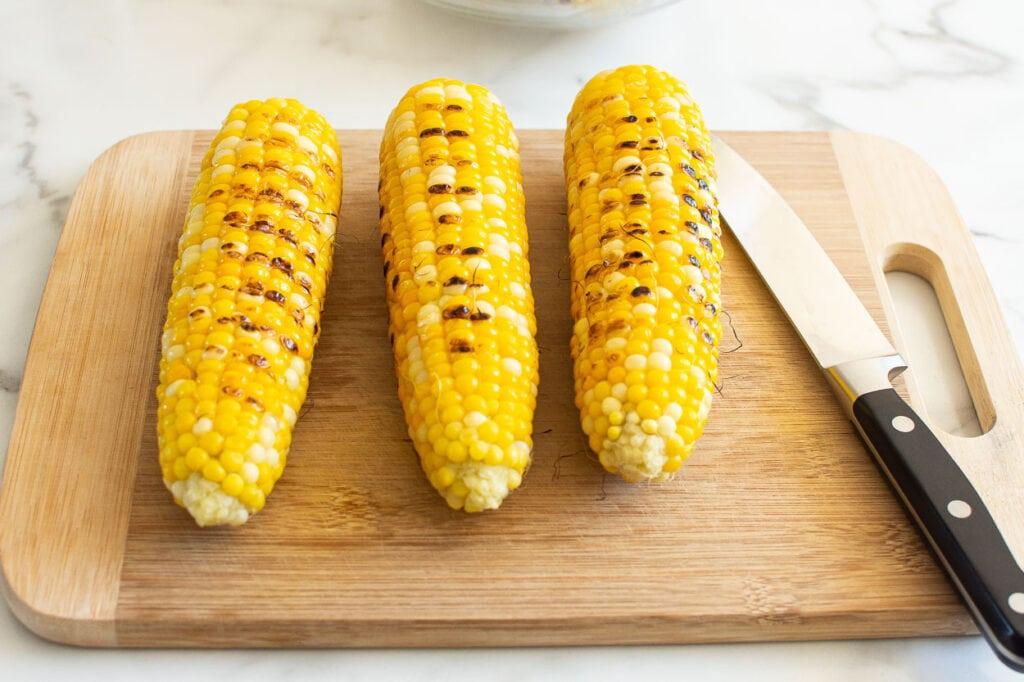 three ears of grilled corn on a cutting board