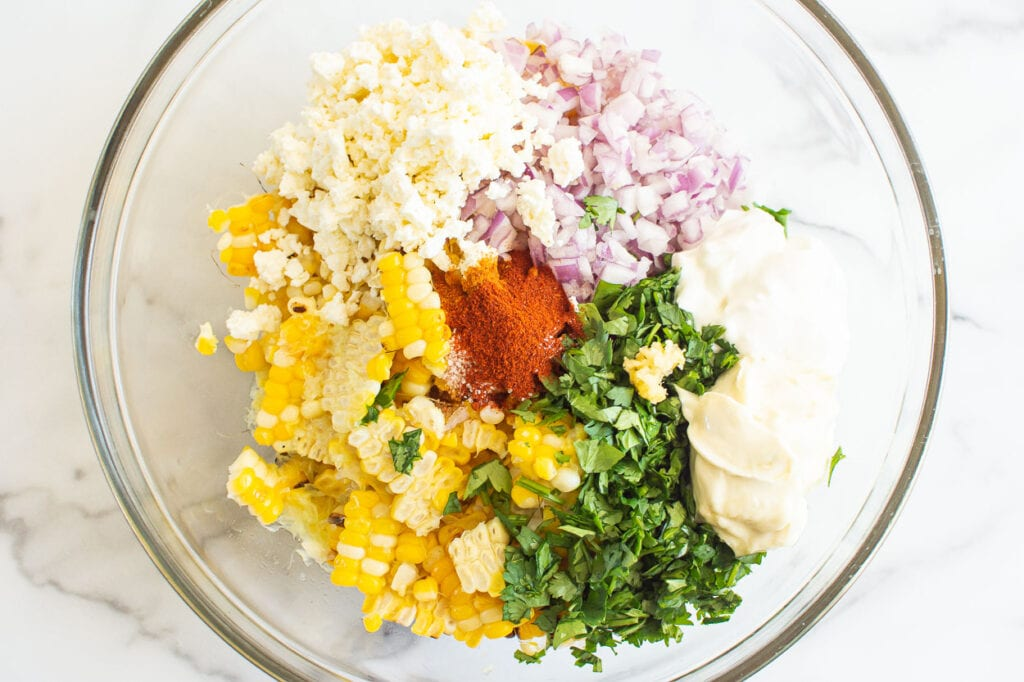cooked corn, cilantro, red onion, feta, mayo, yogurt and spices in glass bowl