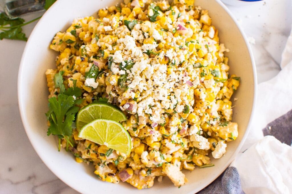 mexican street corn salad with lime wedges and cilantro sprigs