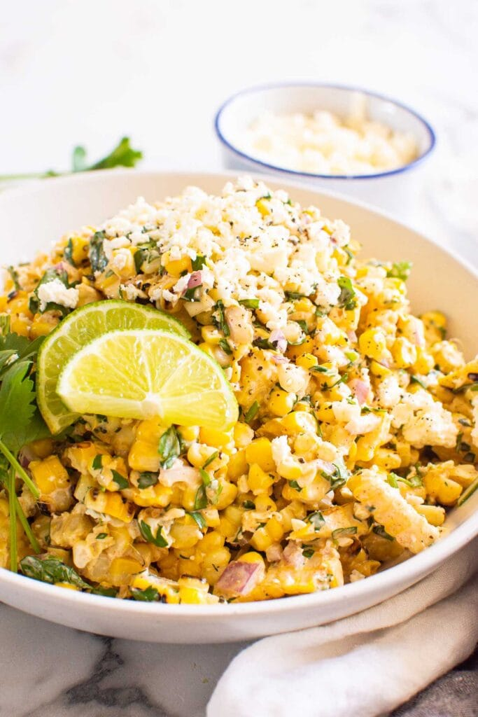 mexican street corn salad served on white plate with feta cheese