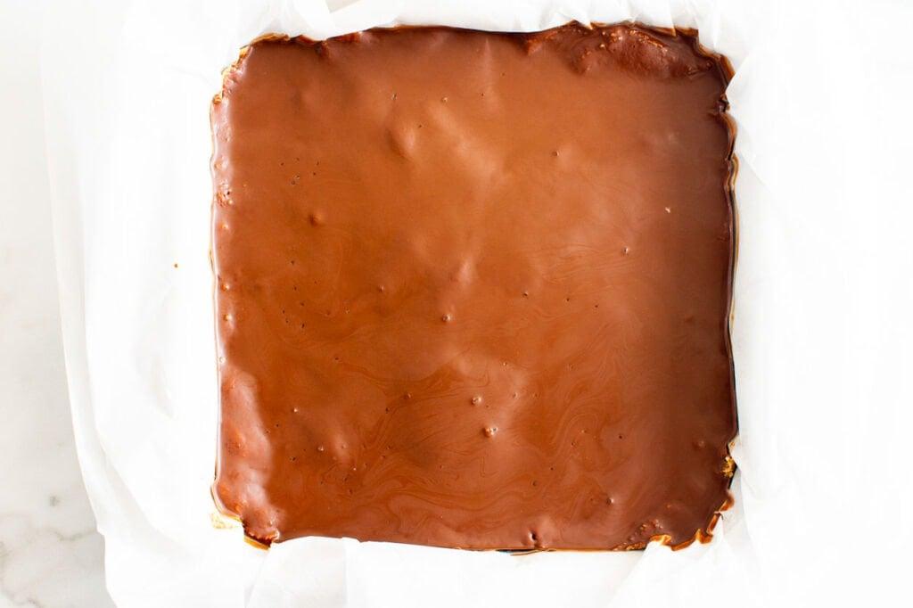 ganache over peanut butter dough in baking tray